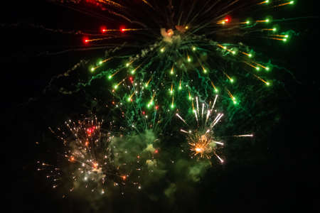 Colorful bright fireworks in dark sky at night. Evening time, low light illumination. Holiday, celebration and anniversary concept Фото со стока