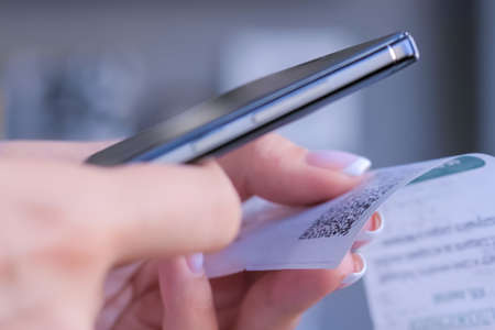 Cash back, sales, online shopping, technology, home accountancy, financial concept. Woman using smartphone and scanning qr code on cash shop receipt paper or bill from store - close up view