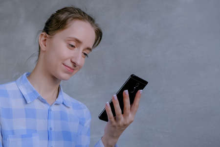 Portrait of woman in blue plaid shirt using black smartphone with touchscreen display in room with grey wall. Entertainment, leisure time and technology concept Фото со стока