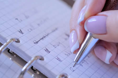Motivation, management, productivity, success, planning, reminder, goals concept. Woman hand putting mark on check boxes of to do list in personal vintage notebook organizer - close up view Фото со стока