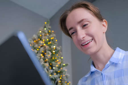 Woman in plaid shirt using laptop, having video chat, job interview or distant consultation in room with Christmas tree. Garland light illumination. Communication, holiday, online technology concept Фото со стока