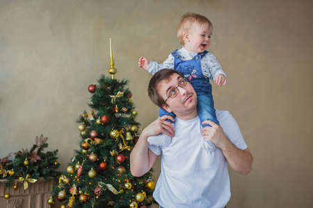 Happy young father carrying smiling son on shoulders against Christmas interior in bright room at home. Family, holiday, childhood and leisure time concept