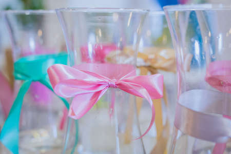 Small empty glass vases for flowers with fabric bow on table at floral studio, flower shop - close up view. Floristry, holiday, celebration, handmade, decoration, small business concept