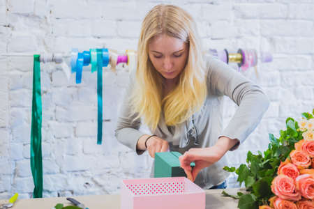 Professional woman floral artist, florist preparing and cutting oasis floral foam for flower arrangement at workshop, flower shop. Floristry, handmade and small business concept