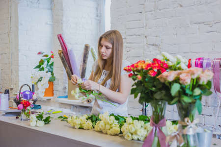 Professional floral artist, florist working with flowers at workshop, flower shop. Floristry, handmade and small business concept Фото со стока