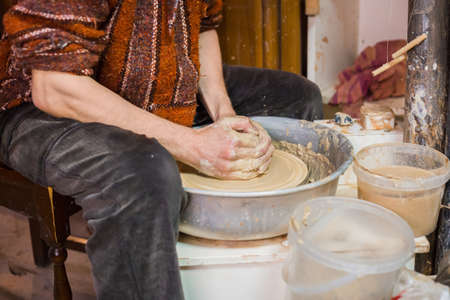 Professional male potter working in workshop, studio. Handmade, small business, crafting work concept