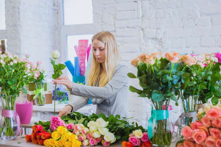 Portrait of professional woman floral artist, florist cutting flowers on table at flower shop, workshop, studio. Floristry, handmade, preparation and small business concept