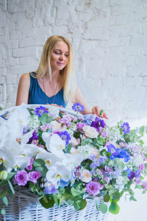 Professional woman floral artist, florist making large floral basket with flowers at workshop, flower shop. Floristry, handmade, wedding, birthday, holiday and small business concept Фото со стока