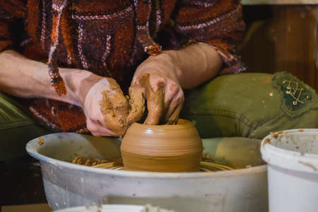 Professional male potter making pot on pottery wheel at workshop, studio. Crafting, artwork, handmade, small business, traditional, manufacturing and handicraft concept
