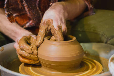 Close up view - professional male potter making pot on pottery wheel at workshop, studio. Handmade, art and handicraft concept