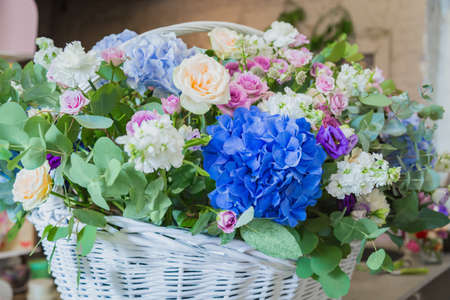 Large floral basket with colorful flowers at workshop, flower shop - close up view. Floristry, holiday, romantic, celebration, handmade and small business concept Фото со стока