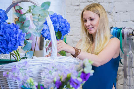 Professional woman floral artist, florist smiling and making large floral basket with flowers at workshop, flower shop. Floristry, handmade, wedding, birthday, holiday and small business concept