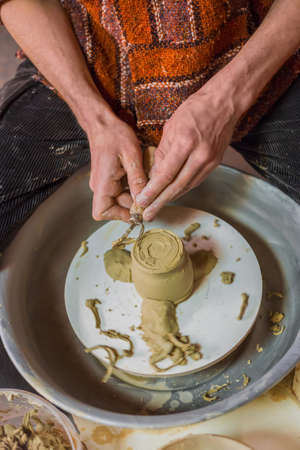 Professional male potter shaping and carving mug with special tool in pottery workshop, studio. Crafting, artwork and handmade concept Фото со стока