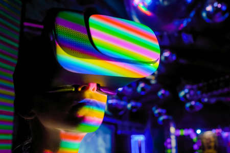 Woman using virtual reality headset, looking around at interactive technology exhibition with multicolor projector light illumination. VR, augmented reality, immersive, entertainment concept