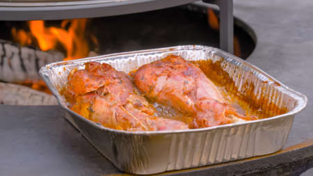Process of cooking roasted turkey legs in disposable aluminium foil container at summer outdoor food market - close up view. Professional cooking, catering, cookery, gastronomy and street food concept