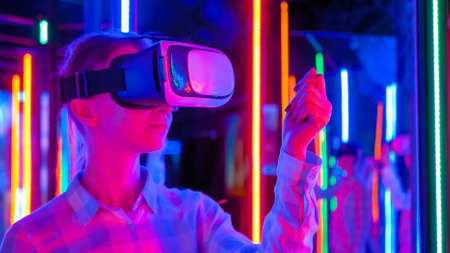 Woman using virtual reality headset and moving hand at interactive technology exhibition with colorful projector light illumination. VR, augmented reality, immersive, entertainment concept