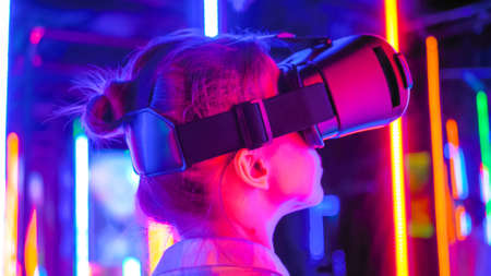 Back view: woman using virtual reality headset and looking right at interactive technology exhibition with colorful illumination. VR, futuristic, retrowave, immersive, entertainment concept