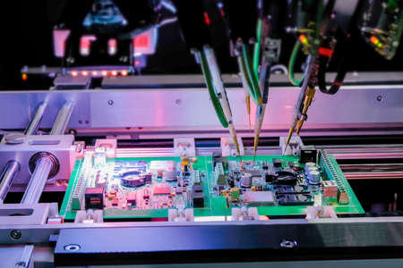 Automated technology, industrial, robotic, electronic, production, manufacturing concept. Automation machine equipment for quality testing of printed circuit boards - flying probe test at factory.