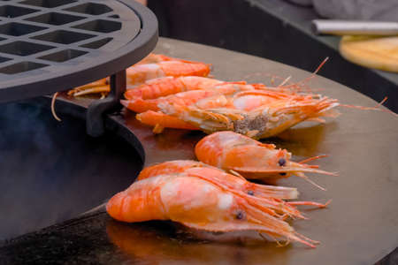 Process of grilling fresh red king prawns on round black brazier at summer local food market - close up view. Outdoor cooking, barbecue, gastronomy, seafood, cookery, street food concept