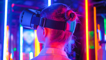 Back view: woman using virtual reality headset and looking left at interactive technology exhibition with colorful illumination. VR, futuristic, retrowave, immersive, entertainment concept