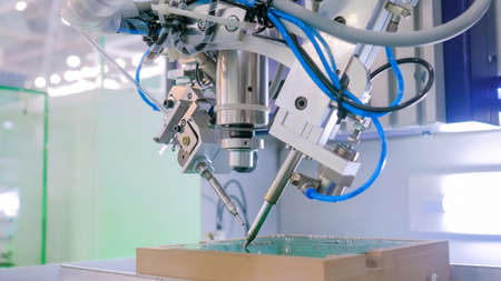 Automated technology, industrial, robotic, electronic, production, manufacturing concept. Close up: process of selective soldering components to printed circuit boards at exhibition, factory