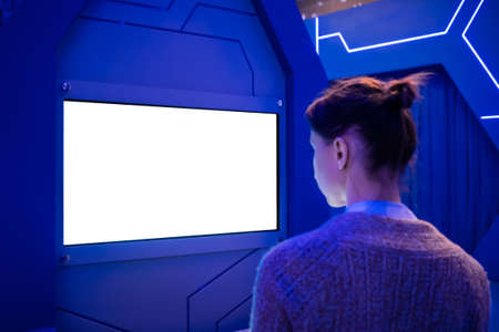 White screen, mock up, future, copyspace, template, technology concept. Woman looking at blank interactive touchscreen white display of electronic kiosk at futuristic exhibition or museum