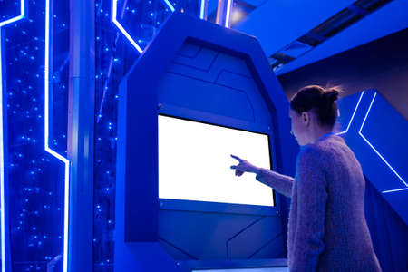 Woman hand using white blank interactive touchscreen display of electronic multimedia kiosk in dark room of scifi museum, exhibition: scroll, touch. Mock up, copyspace, template and technology concept