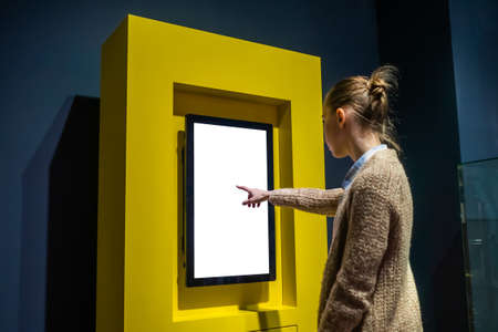 Woman hand using vertical white blank interactive touchscreen display of electronic multimedia kiosk in dark room - scrolling and touching. Mock up, copyspace, template and technology concept Stok Fotoğraf - 165982258