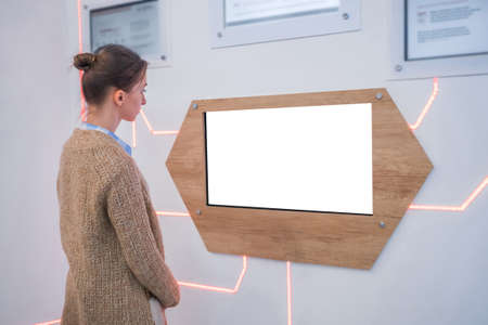 Woman looking at blank digital interactive white display wall at exhibition, museum with futuristic interior. Mock up, sci-fi, future, copyspace, template, white screen, technology concept