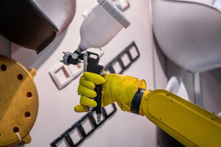 Automatic yellow spray painting robotic arm manipulator demonstrates functionality at smart robot technology exhibition, trade show. Manufacturing, futuristic, production concept