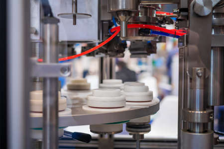 Automatic vacuum capping machine at packaging exhibition, trade show - close up view. Manufacturing, industry, automated technology equipment concept