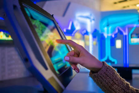 Woman hand using touchscreen display of floor standing tablet kiosk with city map in dark room of museum or exhibition with sci-fi interior: close up side view. Navigation, journey, technology concept Stok Fotoğraf - 165982264