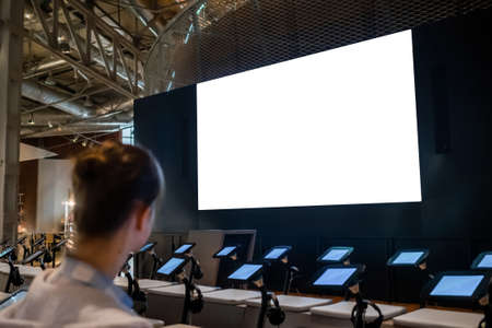 White screen, technology, futuristic, template, mock up, education concept. Woman looking at large blank interactive white display wall at science exhibition, museum or cinema Stok Fotoğraf - 165982267