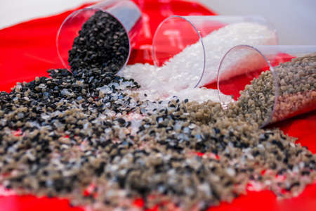 Plastic recycling, renewable resource - heap of secondary polystyrene, polyethylene, polypropylene granules or pellets on red table at exhibition, trade show - close up