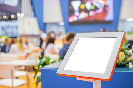 Electronic multimedia tablet kiosk with blank white display at exhibition, trade show, conference - close up view. Mock up, futuristic, corporate, copyspace, template, white screen, technology concept