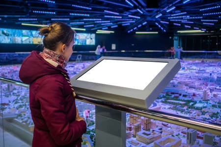 Mock up, copyspace, template, white screen, technology concept. Woman iin jacket looking at blank digital interactive white display kiosk at exhibition or museum with futuristic sci-fi interior Stok Fotoğraf