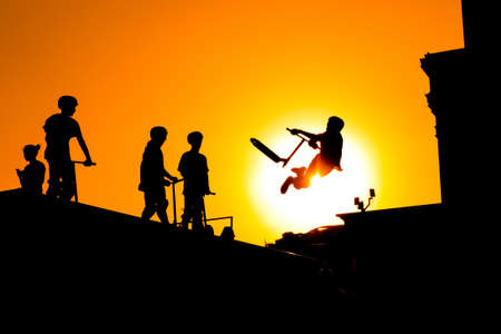 Unrecognizable teenage boy silhouette showing high jump tricks on scooter against orange sunsetwarm sky at skatepark. Sport, extreme, freestyle, outdoor activity concept