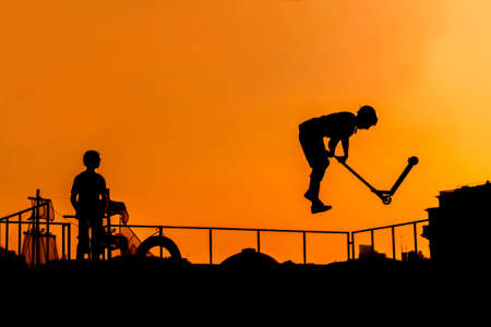 Unrecognizable teenage boy silhouette showing high jump tricks on scooter against orange sunset sky at skatepark. Sport, extreme, youth, urban culture, freestyle, outdoor activity concept