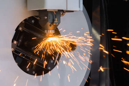 Automatic cnc laser cutting machine working with cylindrical metal workpiece with sparks at factory, plant. Metalworking, machining, industrial, equipment, technology, manufacturing concept Stok Fotoğraf