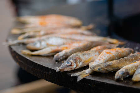 Process of cooking european smelt fish with red paprika powder on black brazier at summer outdoor food market: close up. Seafood, barbecue, gastronomy, cookery, street food concept Stok Fotoğraf - 166627052