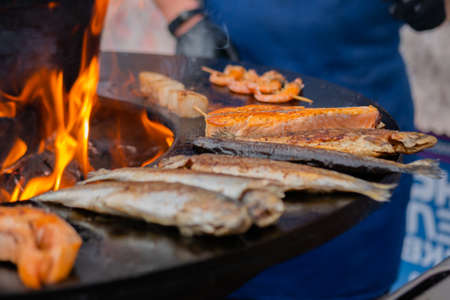 Process of grilling salmon steaks and mackerel fish on black brazier with hot flame at summer local food market - close up. Outdoor cooking, barbecue, gastronomy, seafood, cookery, street food concept