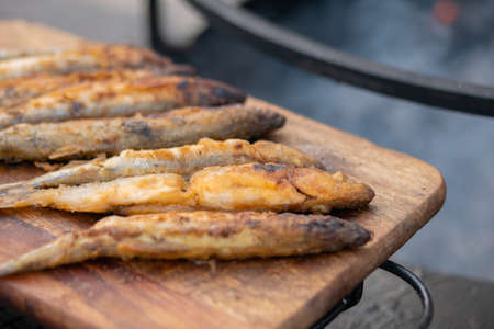 Crispy breaded european smelt fish on wooden cutting board at summer outdoor food market: close up. Seafood, barbecue, gastronomy, cookery, street food concept Stok Fotoğraf
