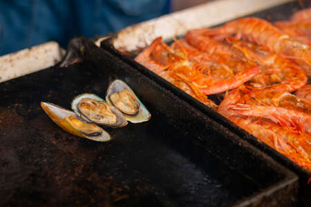 Process of cooking mussels, clams and red langoustine shrimps, prawns on grill at summer local food market - close up. Outdoor cooking, barbecue, gastronomy, seafood, cookery, street food concept Stok Fotoğraf