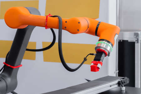 Orange pick and place robotic clamp arm manipulator moving red toy blocks at modern robot trade show, exhibition. Manufacturing, engineering, industrial, ai, automated technology concept