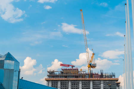 Moving yellow tower cranes and unfinished building construction against summer cloudy blue sky. Building process, architecture, urban, engineering, city developing industrial concept Stok Fotoğraf