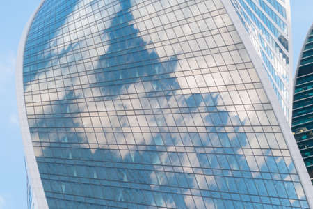 Reflection of white clouds and blue sky in glass wall of modern tall building, skyscraper - low angle view. Architecture, corporate, business, financial, urban, cityscape concept Stok Fotoğraf - 166627591