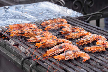 Process of cooking fresh red langoustine shrimps, prawns on grill at summer local food market - close up. Outdoor cooking, barbecue, gastronomy, seafood, cookery, street food concept