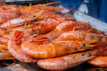 Close up: process of cooking fresh red langoustine shrimps, prawns on grill at summer local food market. Outdoor cooking, barbecue, gastronomy, seafood, cookery, street food concept