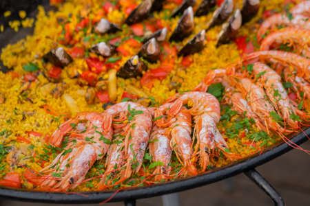 Close up: cooked yellow paella with shrimp, mussel, rice, spice, saffron in huge paella pan at summer outdoor food market. Spanish cuisine, seafood, gastronomy, street food concept