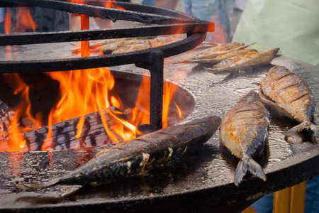 Process of grilling mackerel fish on black brazier with hot flame at summer food market: close up. Seafood, barbecue, gastronomy, cookery, street food and outdoor cooking concept Stok Fotoğraf - 166628073